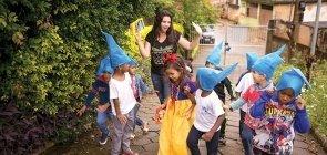 Ela olha para crianças que andam na sua frente. No centro uma menina com vestido amarelo e azul e laço vermelho na cabeça, meninos com uniforme um chapeu pontudo azul