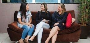 Sentadas em um sofá preto, três mulheres conversam