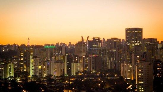 Entardecer na zona sul de São Paulo, de céu laranja sobre uma grande massa de prédios em sua maioria brancos. É possível notar um pedaço da ponte estaiada, um dos símbolos recentes da cidade.
