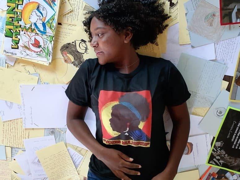 Uma das alunas da professora Camile Baccin de Moura deitada em meio aos trabalhos inspirados pelas obras lidas no projeto