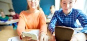 Jovens usam celular em sala de aula