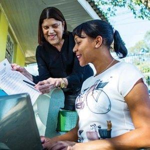 Em primeiro plano uma mulher com um computador sorri e olha para onde aponta mulher em pé