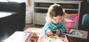 Bebê olha para páginas coloridas de livro infantil
