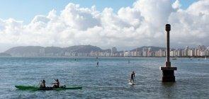 mar de Santos com duas pessoas remando sentadas em um caiaque e uma pessoa fazendo stand-up paddle ao lado de um sinalizador de concreto. Ao fundo, os prédios da orla e montanhas.