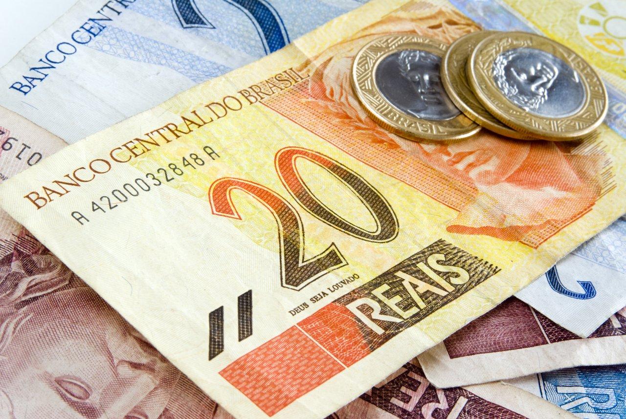 Notas de real e moedas empilhadas