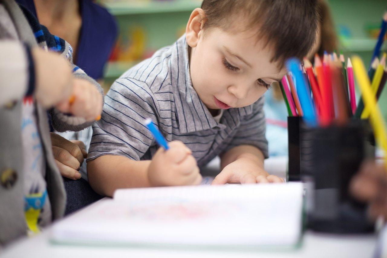 Criança desenha com canetas coloridas apoiada em uma mesa