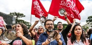 Professores do Paraná de panelas e colheres em mãos com bandeiras da CUT ao fundo
