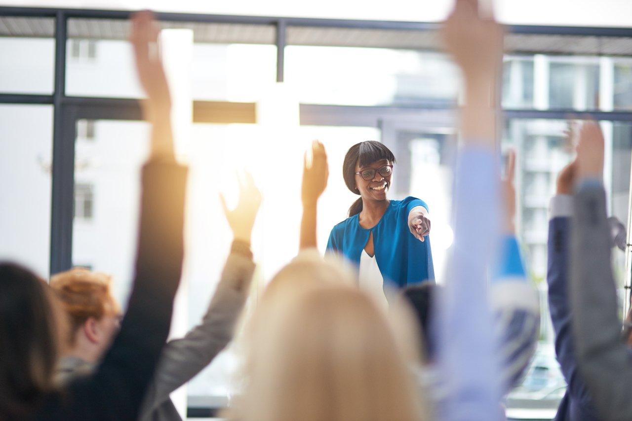 Professora em meio aos alunos com mãos levantadas em sala de aula