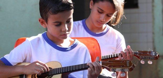 Nas duas aulas semanais que Alessandro tinha com cada uma das turmas da escola, ele propôs aos alunos que experimentassem diferentes instrumentos. Passadas algumas aulas, cada aluno escolheu seu instrumento de estudo. O Rafael, na foto, escolheu o cavaquinho e aprendeu a ler a música no sistema de tablatura. Foto: Marco Monteiro