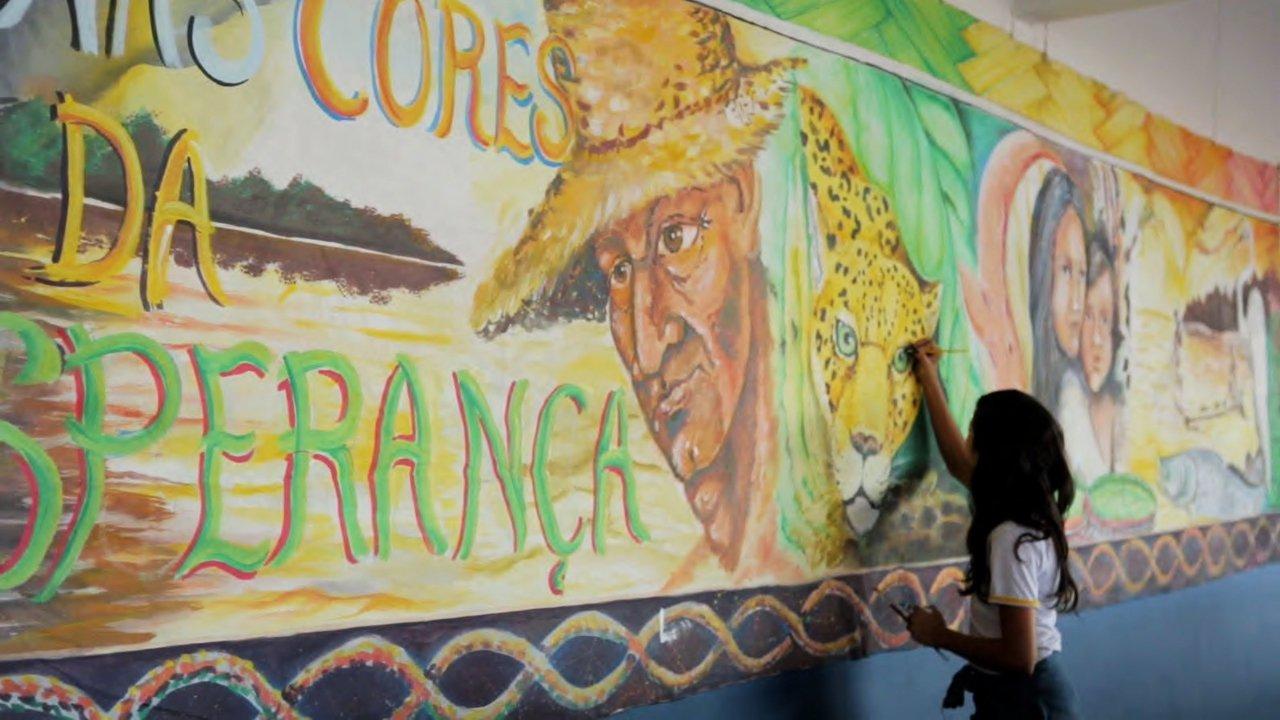 Aluna da EM Antônio Matias Fernandes faz pintura nas paredes do corredor da escola de Manaus (AM)