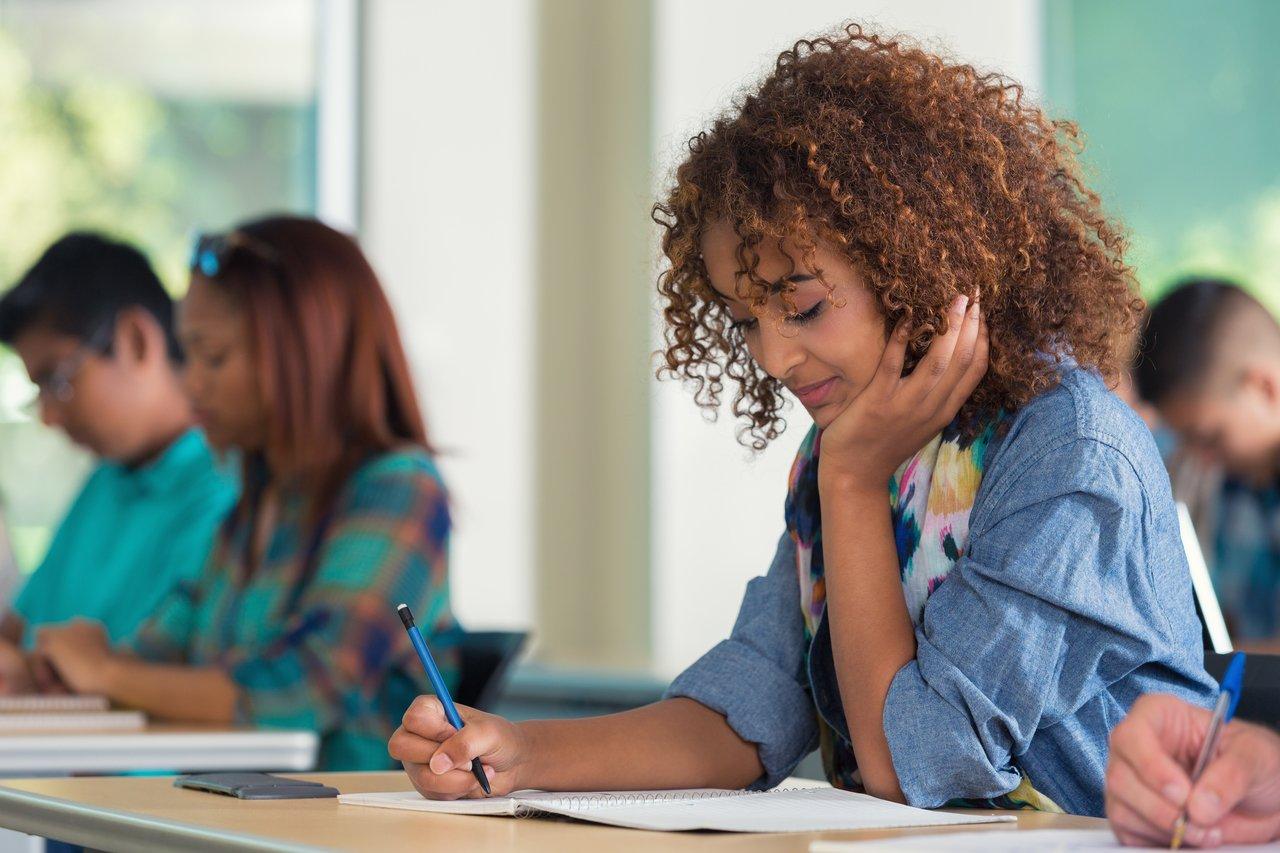 Menina sentada em uma mesa escrevendo em um caderno