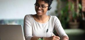 Mulher sorridente em fones de ouvido estudando fazer anotações