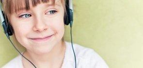 Menino ouve programa de podcast com fone de ouvido