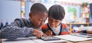Dois meninos de cerca de oito anos sentados em dupla e mexendo em um tablet na sala de aula