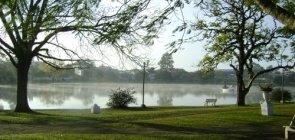 Área verde com árvores e uma grande lagoa ao fundo