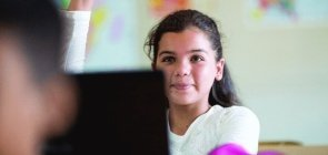 Alunos usam ferramentas digitais durante aula: menina ergue o braço para fazer perguntas