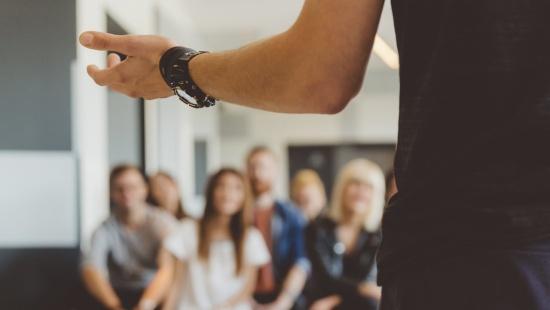 grupo de professores desfocados olham para uma pessoa que está palestrando para eles em primeiro plano