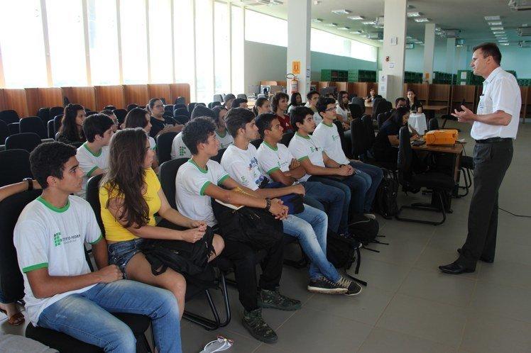 Fila de jovens sentados em cadeiras ouvindo professor falar à frente, de pé