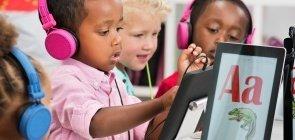 Crianças sentadas em mesas de escola e usando fones de ouvido brincam com tablets que exibem letras coloridas