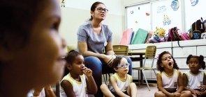 Sentadas no chão, as crianças vestem uniforme e prestam atenção, ao lado uma professora também acompanha a atividade