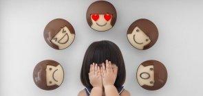 uma menina de cerca de cinco anos cobrindo o rosto. Há cinco emoticons ao entorno de sua cabeça mostrando reações de tristeza, risada, apaixonada, feliz e surpresa