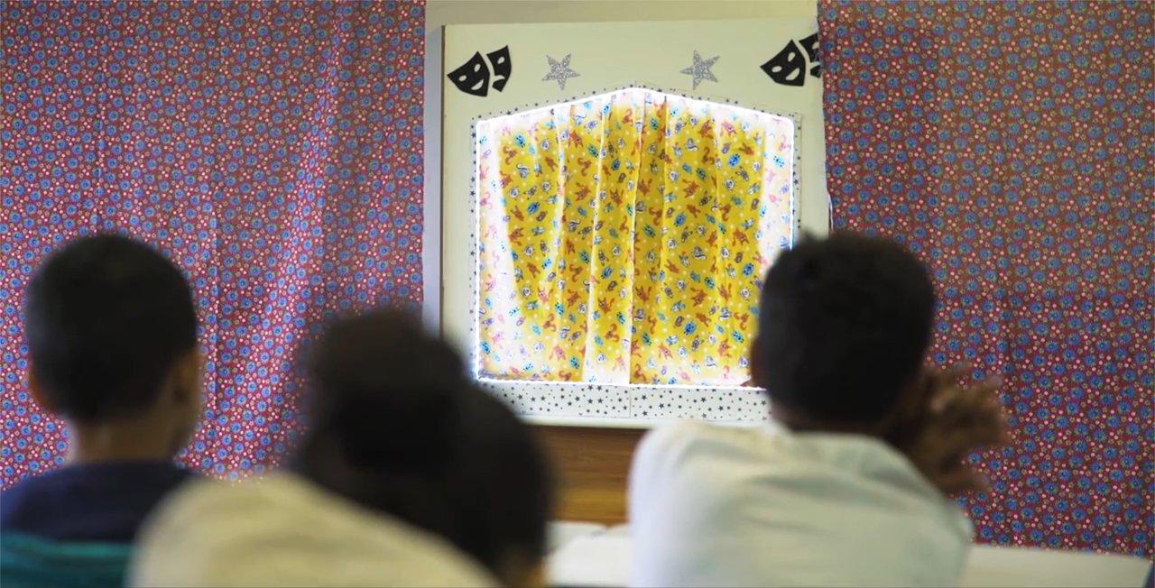 Crianças assistem a um teatro de fantoches em escola de São Paulo