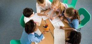Crianças reunidas escrevem