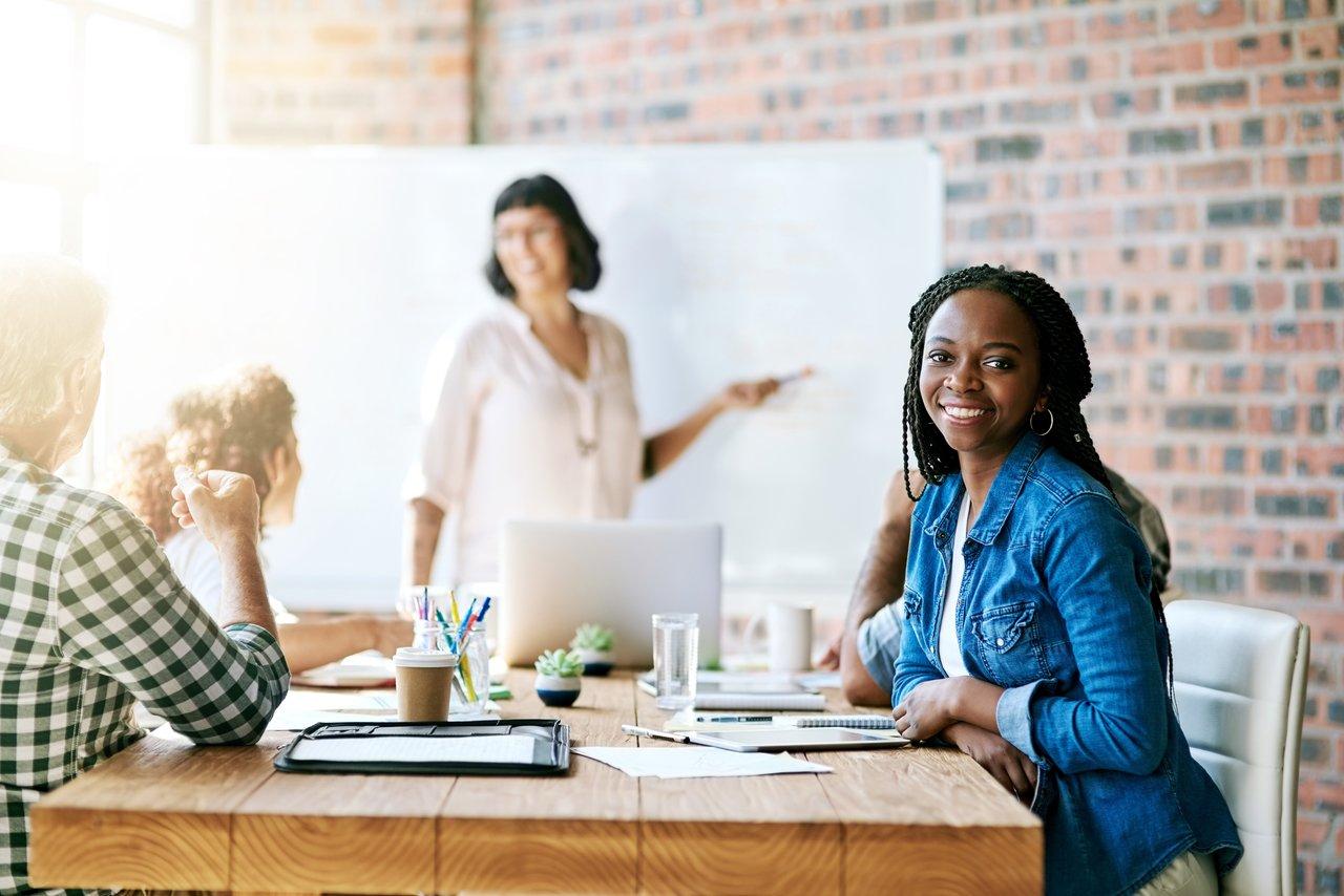 Pessoas reunidas em volta de uma mesa, uma mulher de pé explica algo em um quadro, outra, sentada, olha para a câmera e sorri
