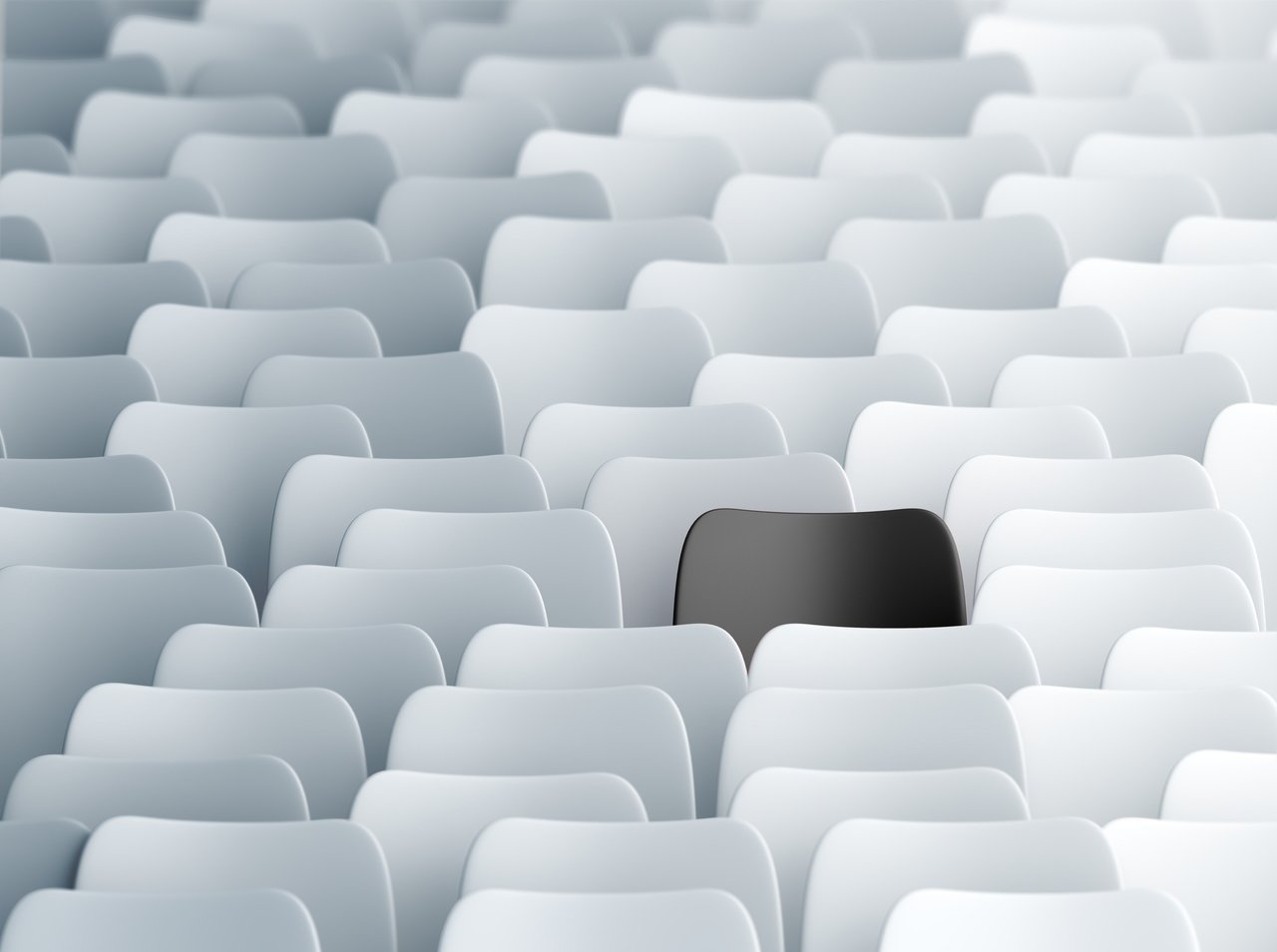 Grupo de cadeiras brancas. Ao centro, uma cadeira preta se destaca.