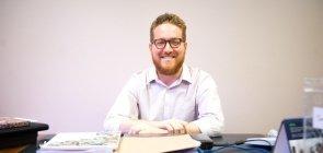 Um homem de 36 anos ruivo, com óculos e de barba sentado com as mãos sobre a mesa, que está cheia de papéis