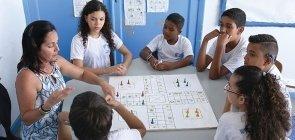 Em uma mesa, seis alunos olham para a professora que está na ponta e apresenta um jogo de tabuleiro que está no centro da mesa