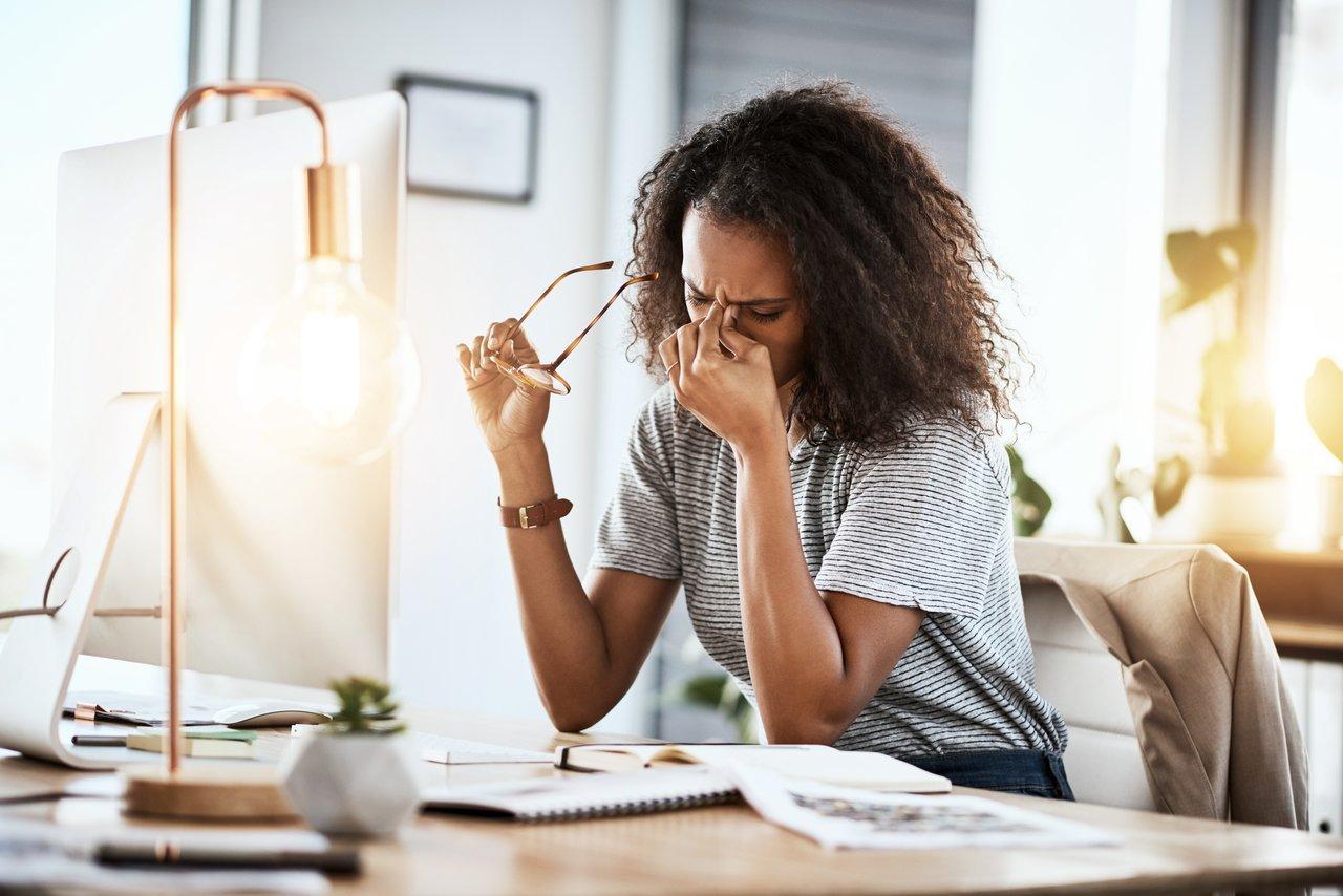 Mulher sentada em uma mesa em frente a um monitor de computador tira os óculos e segura entre os olhos com uma das mãos em uma expressão de cansaço