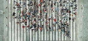 Grupo de pessoas paradas em pé, em cima de uma faixa de pedestres, usando roupas coloridas e vistas de cima, formando a imagem de um balão de fala de histórias em quadrinhos