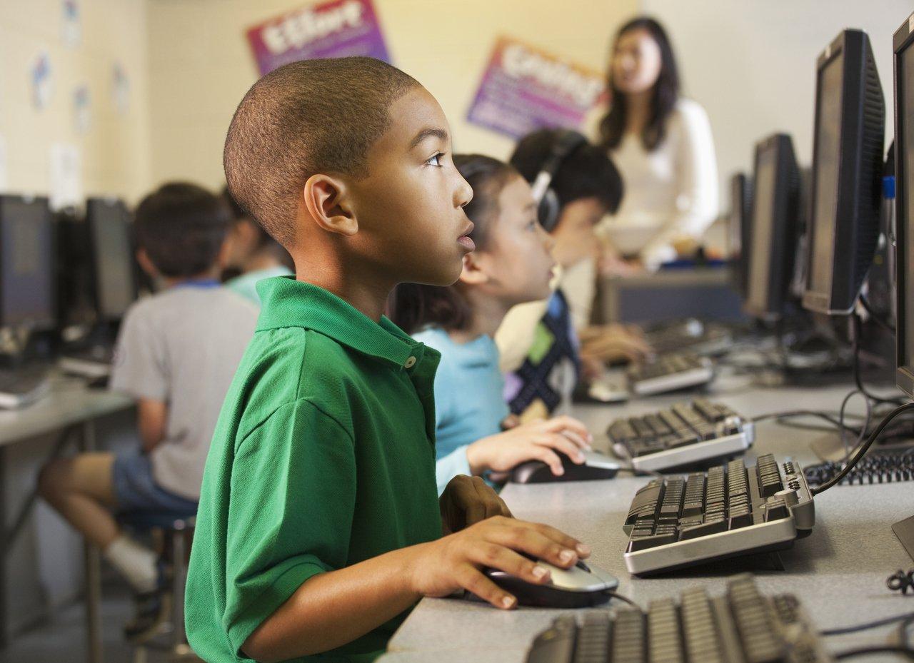 Menino olha atentamente para tela do computador enquanto usa o mouse em uma sala de aulas com outros computadores, alunos e professora ao fundo