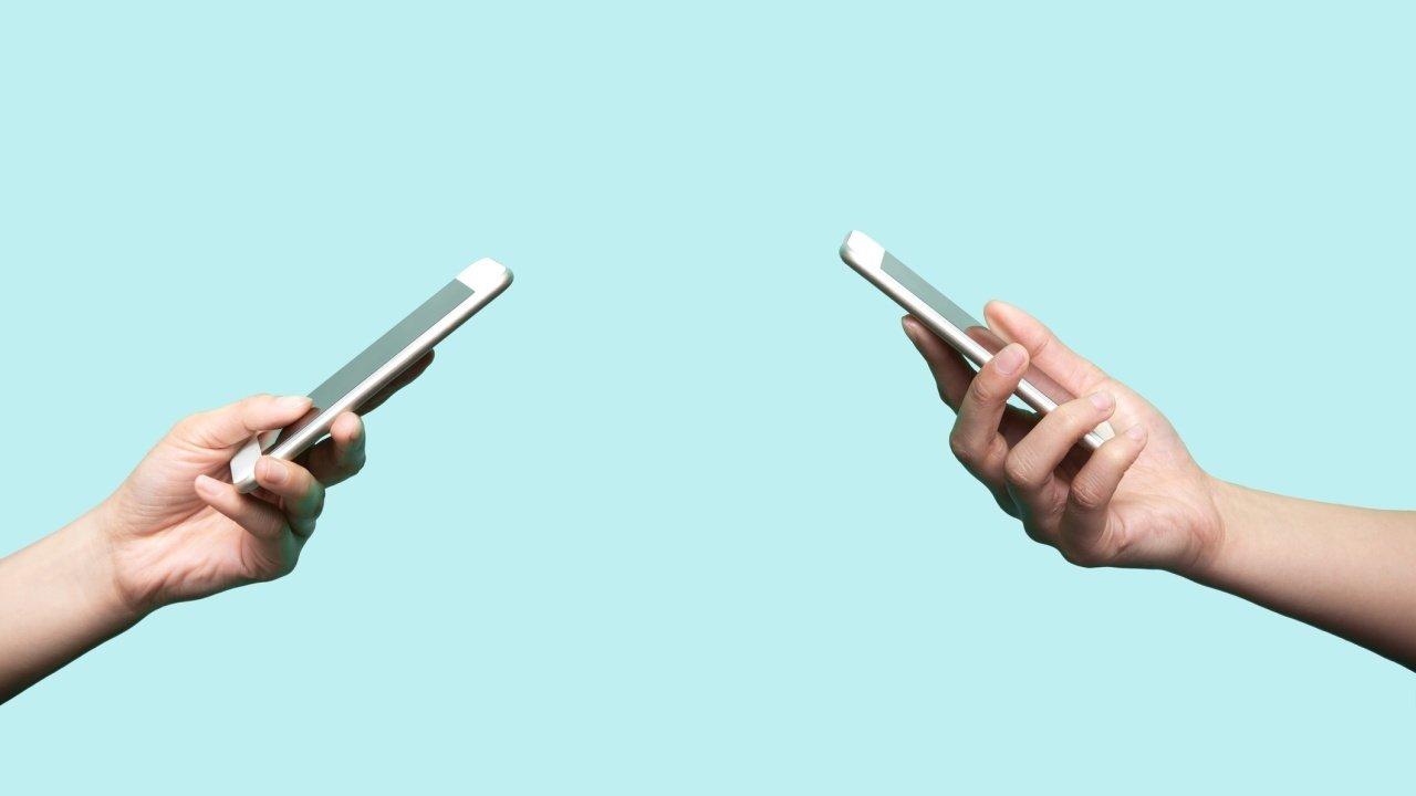 Num fundo azul claro, duas mãos de pessoas diferentes seguram um celular
