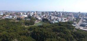 vista da cidade de Farroupilha. Vê-se no canto inferior da foto uma grande área verde e muitos prédios no horizonte