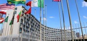 Vista lateral da sede da Unesco, em Paris, em que pode-se ver parte do prédio construído em formato semi-cicular e as bandeiras de 10 países