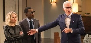 Três pessoas, mais à direita uma mulher loira, ela está surpresa. Ao seu lado, um homem negro, usando oculos e terno completo à dua direita um homem mais velho de cabelo branco e oculos usa terno azul