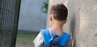 Aluno de costas, com uma mochila nos ombros, apoiado em um muro cinza