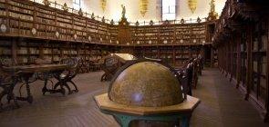 Globo terrestre envelhecido dentro de um prédio antigo com dois andares de prateleiras de livros