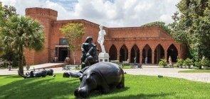 Foto do Instituto Brennand, uma área verde com monumentos e ao fundo uma estrutura de tijolos