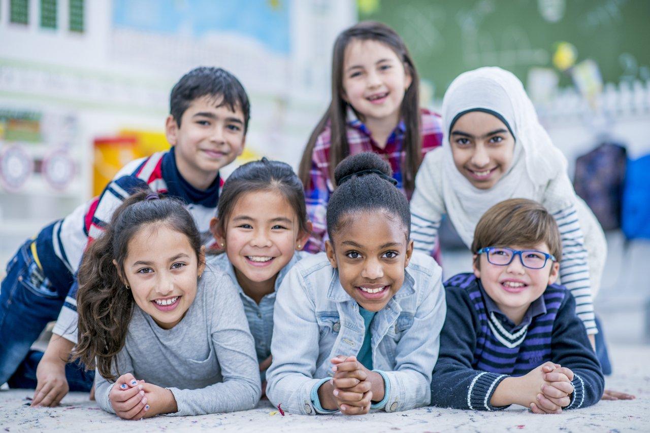 Alunos de várias nacionalidade juntos e sorrindo em uma sala de aula