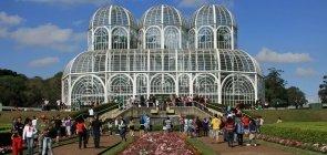 Estufa com estrutura branca enfeitada por jardim na frente e muitos turistas em volta