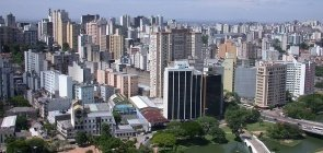 Foto aérea de Porto Alegre. Há prédios, uma via principal e áreas verdes