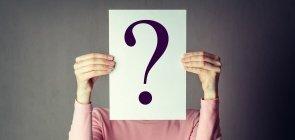 Uma mulher cobrindo o rosto com papel que tem um ponto de interrogação