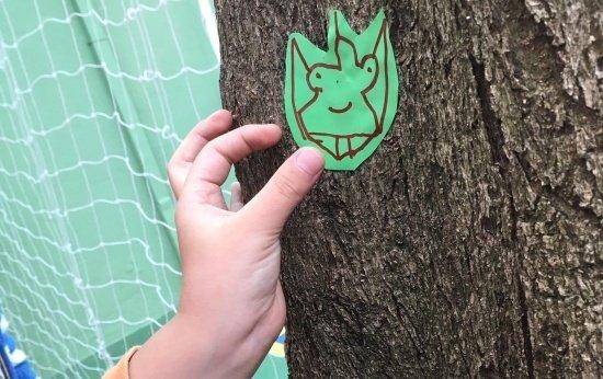 Imagem mostra uma mão de uma criança de cerca de 7 anos colando um papel adesivado com desenho de um mutante em um tronco de árvore