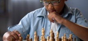 Estudante pensa diante d um tabuleiro de xadrez