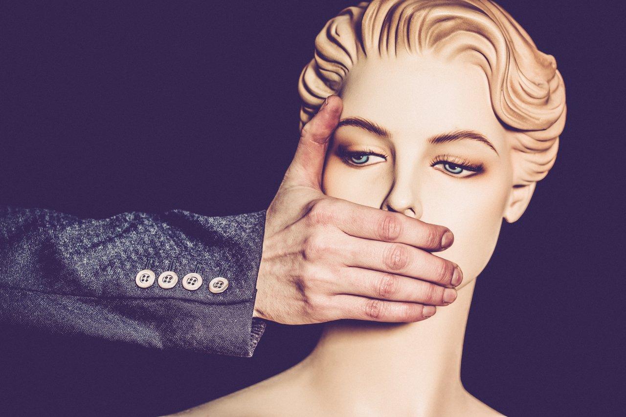 Mão de homem usando terno tampa boca de manequim feminina em frente a um fundo roxo