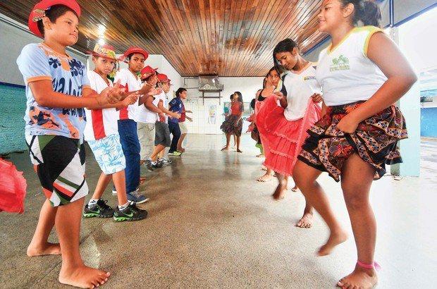 Os garotos marcam o ritmo da música batendo palma e também os pés no chão. Marcos Negrini/Agência Phocus