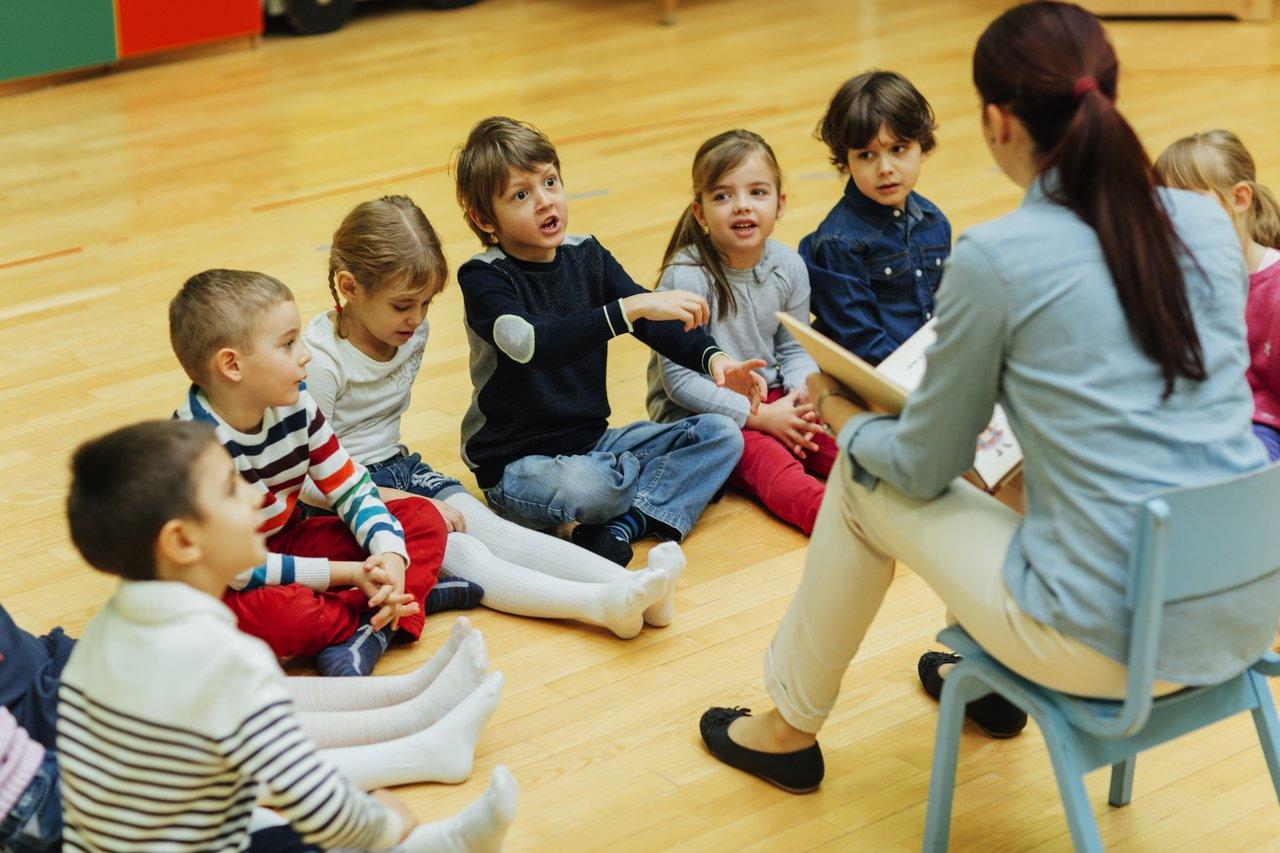 Uma professora sentada em uma cadeira lê e mostra o livro para alunos sentados em semicírculo no chão de tábuas de madeira clara